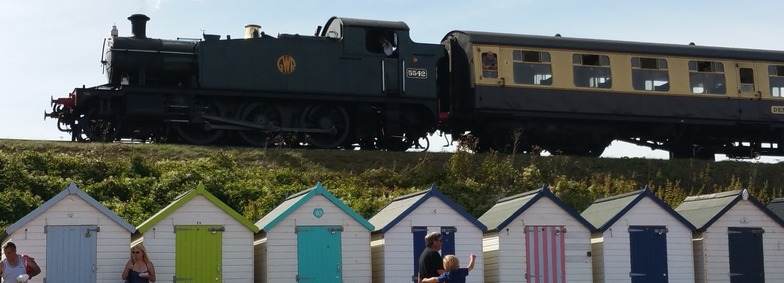 The steam train passing the beach huts at Goodrington sands